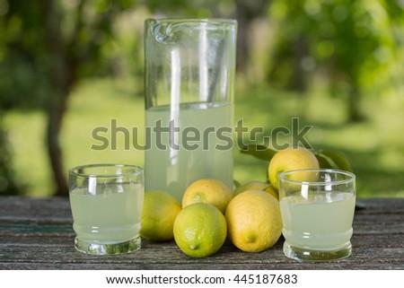 lemon juice on a wooden table, summer set, outdoor - stock photo