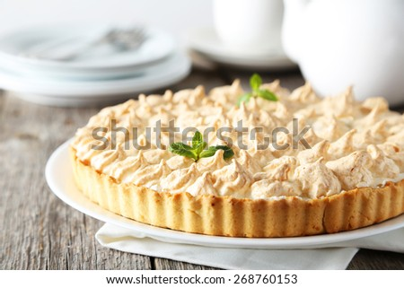 Lemon meringue pie on plate on grey wooden background - stock photo