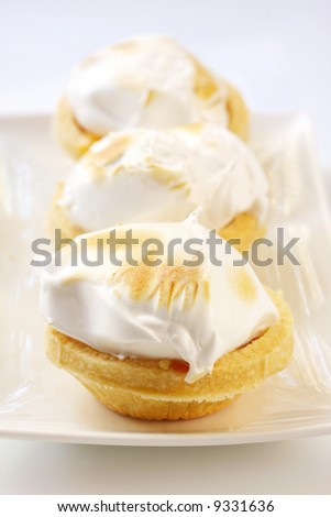 Lemon meringue tarts, on white rectangular serving plate.  Sweet dessert treats. - stock photo