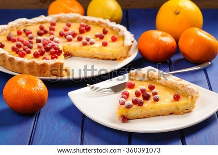 Lemon pie with condensed milk decorated with fresh cranberries on deep blue table - stock photo