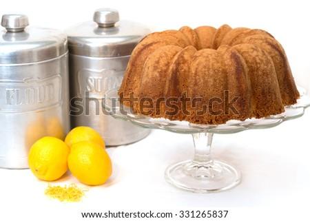 Lemon pound cake with lemons, lemon zest, flour and sugar canisters. - stock photo