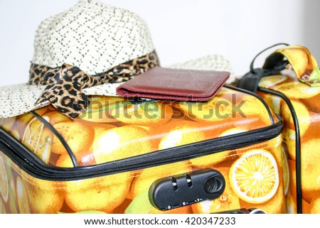 Lemon print suitcase packed ready to take on holiday with sunhat and passport - stock photo