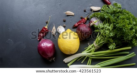 lemon, red onion, green onions, herbs, parsley, chilli, pepper spices pepper on a black background. Overhead view . Frame with fresh organic vegetables and herbs. Healthy eating and cooking concept - stock photo