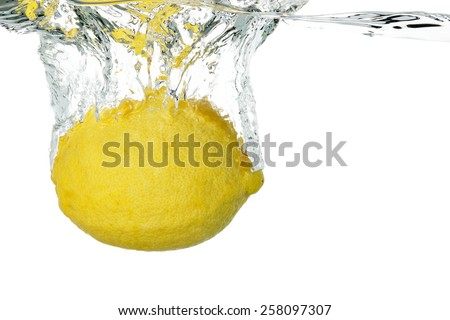 lemon sinking into water on white - stock photo