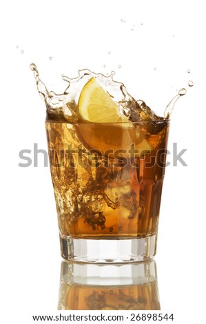 lemon slice falling in to glass with ice tea - stock photo