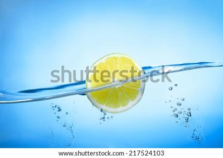 Lemon Slice in water on blue background - stock photo