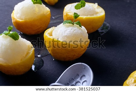 Lemon sorbet or ice cream inside fresh lemons decorated with mint leaves. Dark wood background with ice cream spoon on back - stock photo