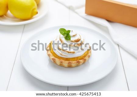 Lemon tart with whipped cream and mint sweet dessert on white plate - stock photo