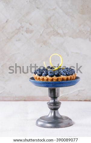 Lemon tartlet with fresh blueberries and lemon zest, served on vintage cake stand over white tablecloth. - stock photo