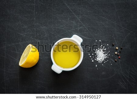 Lemon vinaigrette dressing ingredients on black chalkboard background from above. Lemon, olive oil, salt and pepper. Layout with free text space. - stock photo