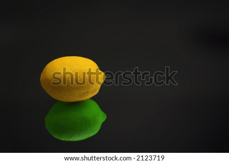 Lemon with lime reflection - stock photo