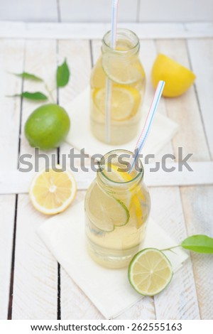 Lemonade in jar with slices of lime and lemon - stock photo