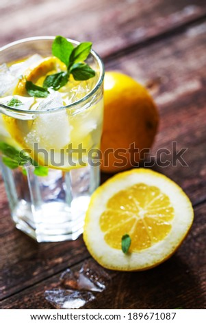 Lemonade with fresh lemon and mint on wooden table - stock photo