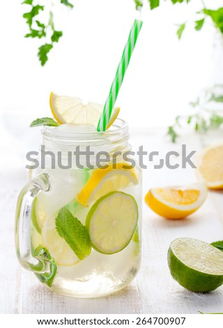 Lemonade with ice, lemon and lime slices in a jar with straw in a white summer woodenbackground - stock photo