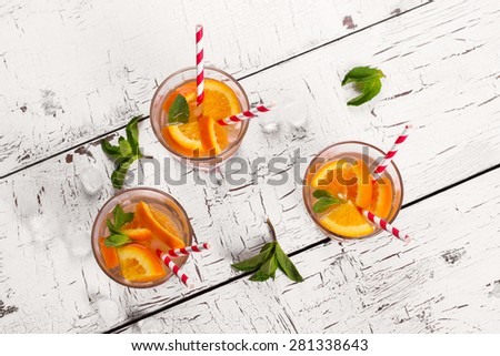 Lemonade with orange, soda and mint on white wooden table, top view - stock photo
