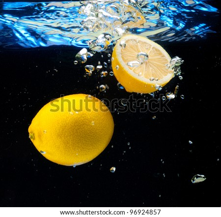 Lemons floating in the water on a black background - stock photo