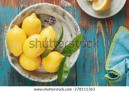 Lemons. Fresh lemons with leaves in  rustic ceramic bowl over wooden background. Macro, selective focus, vintage style. Natural light - stock photo