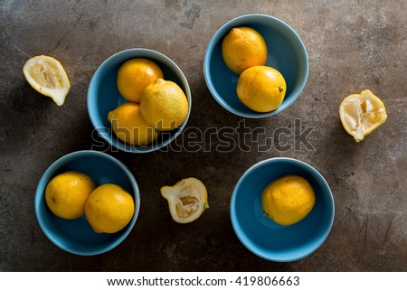 Lemons in bowls on rustic surface - stock photo