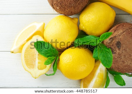 Lemons, mint, coconut and banana on a white wooden table. Fruit concept. Yellow tropical colors fruits. - stock photo
