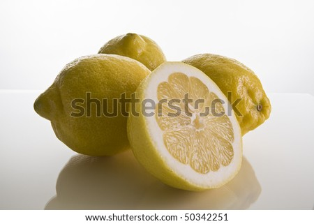 Lemons on a white background with one cut open - stock photo