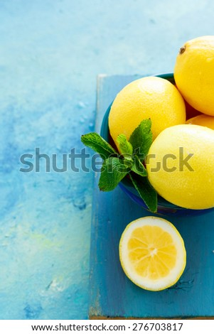 Lemons Whole and sliced placed against a blue - green background , with some mint leaves - stock photo