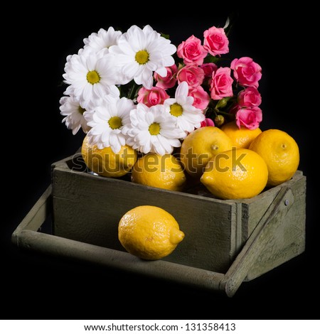 Lemons with flowers in the wood box, isolated on black - stock photo
