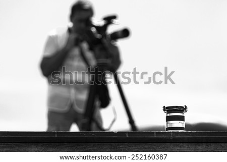 Lens and Cameraman,black and white - stock photo