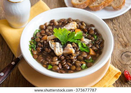 Lentil soup with chicken and vegetables in white bowl close up - stock photo