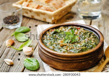 Lentil spinach soup on a dark wood background. the toning. selective focus - stock photo