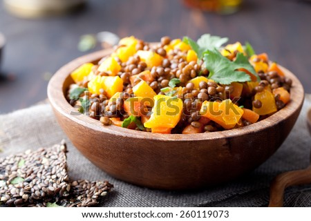 Lentil with carrot and pumpkin ragout in a wooden bowl on a wooden background - stock photo