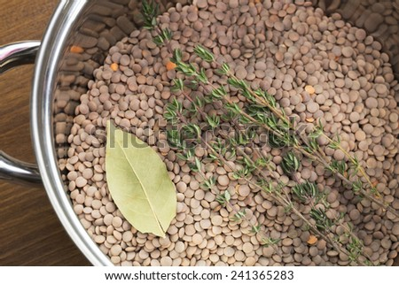 Lentils, thyme and bay leaf in pot, ready for cooking. - stock photo