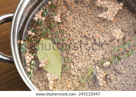 Lentils, thyme and bay leaf in pot with water, ready for cooking. - stock photo