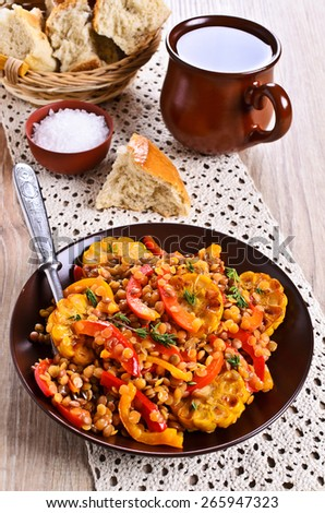 Lentils with paprika and corn in a ceramic plate painted on a wooden surface - stock photo