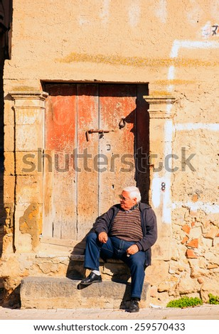 LEONFORTE, ITALY - JANUARY, 08: Old man sitting on the step of old door on January 08, 2014 - stock photo