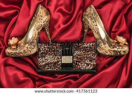 Leopard shoes and purse lying on the red satin, top view - stock photo