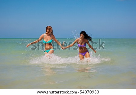 Lesbian girls running in the ocean - stock photo