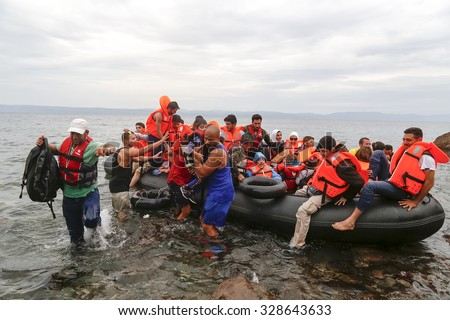 Lesbos, Greece, Oktober 11 2015: Refugees and Migrants aboard dinghies reach the Greek Island of Lesbos after crossing the Aegean sea from Turkey  - stock photo