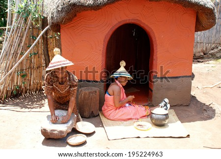 LESEDI,SOUTH AFRICA - JAN 1, 2008:Sotho women in handmade dress and conical hat cooking maize meal and weave beaded jewelry at tribal house at Lesedi Cultural Village,South Africa. - stock photo