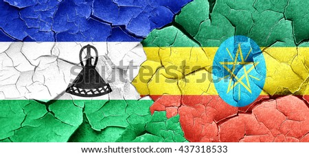 Lesotho flag with Ethiopia flag on a grunge cracked wall - stock photo