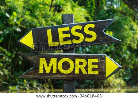 Less - More signpost with forest background - stock photo