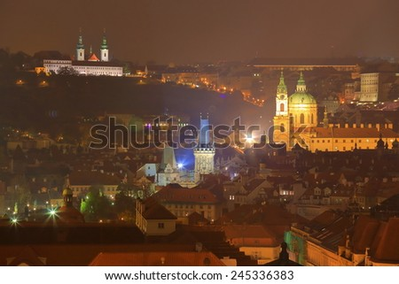 Lesser Town with church towers illuminated in autumn night, Prague, Czech Republic - stock photo