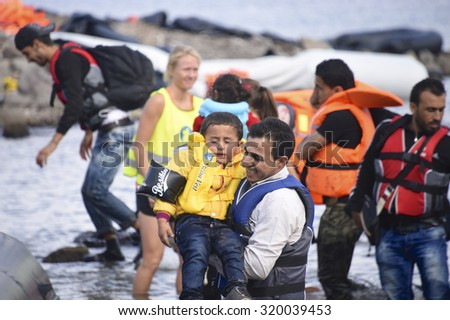 LESVOS, GREECE SEPTEMBER 24, 2015: Refugees arriving in Greece by boat from Turkey.  These Syrian refugees are helped, by Norwegian volunteers, to land their boat near Molyvos, Lesvos (Mytilene). - stock photo