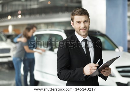 Let me assist you in your vehicle search. Handsome young classic car salesman standing at the dealership with the customers on the background - stock photo