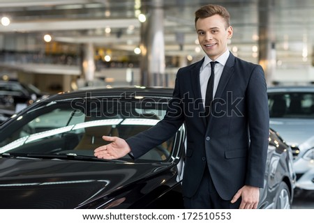 Let me show our new model. Handsome young classic car salesman standing at the dealership and pointing car - stock photo