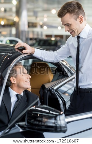 Let me show you all the features. Confident mature man ion formalwear sitting at the front seat of the car and talking to the car salesman standing near him - stock photo