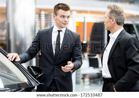 Let me show you interior of this car. Handsome young classic car salesman standing in the dealership and helping a client to make a decision about car - stock photo