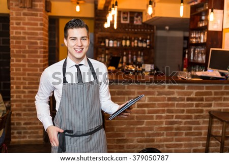 Let me show you our menu. Barista holding tablet PC. Selective focus, depth of field - stock photo