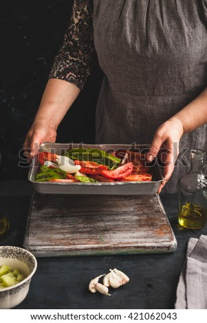 Letcho or gazpacho preparation in cooking sheet.  Female hand  preparing mix vegetables meal. Rustic dark styling. Copy space  - stock photo