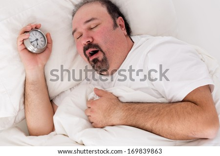 Lethargic tired man lying in bed yawning as he struggles to wake up unmotivated to start the new day and content to rather continue lying in bed as he holds his alarm clock in his hand - stock photo