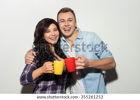 Lets drink tea and warm together. Beautiful young loving couple is standing and holding cups. They are embracing and smiling. Isolated on background - stock photo